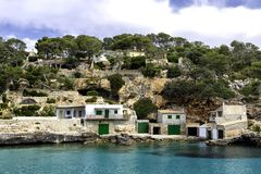 A view of houses with boat garages and azure sea water, Cala Llombards, Mallorca island. Spain Royalty Free Stock Images