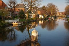 View of houses, drawbridge and boats along a canal in the historic town of Edam, Netherlands. Calm scene on sunny spring day royalty free stock image