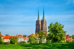 View of houses and St. John Cathedral towers on Tumski Island. With green trees and lawn. Cityscape of  Wroclaw, Poland, summer, blue sky Royalty Free Stock Image
