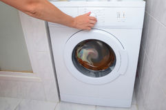 View on how a woman is turning on of the washing machine. A woman is choosing a washing mode on the washing machine.  Stock Photography