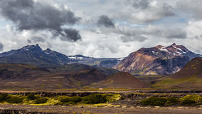 View on a huge mountain and small house in Iceland with dramatic sky Stock Photos