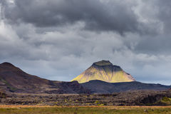 View on a huge mountain and small house in Iceland with dramatic sky Stock Photo