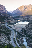 View of hydro-electric power station and a highway. Dam at Sege river, Oliana, Spain, Europe. Mountain peaks landscape. Stock Photos
