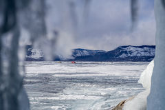 View from ice cave at car crossroad on frozen lake Baikal Royalty Free Stock Image