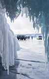 View from ice cave at cars on frozen lake Baikal with mountains Royalty Free Stock Photo
