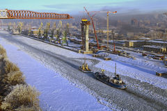 View of ice-covered sea canal cargo port and small vessels. Royalty Free Stock Image