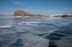 View of ice covered water surface of lake and rock formations on background, Russia,. Lake Baikal stock image