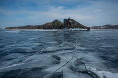 View of ice covered water surface of lake and rock formations on background, Russia,. Lake Baikal royalty free stock image