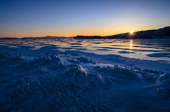 View of the ice and the rising sun over the mountains, lake Baikal royalty free stock images