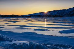 View of the ice and the rising sun over the mountains, lake Baikal royalty free stock photography