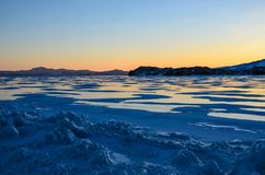View of the ice and the rising sun over the mountains, lake Baikal stock photo
