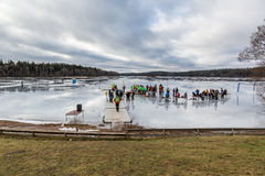 View of ice skaters and volunteers one a frozen lake with green grass in the foreground. stock images