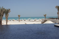View of an idyllic beach from an infinity pool Royalty Free Stock Photography