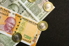 View Indian currency, 200, 500 and one rupees note with coins on black background stock photo