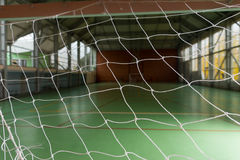 View of an indoor sporting facility. View of an empty indoor sporting facility with an all weather green court viewed through the net in the goal Stock Photography