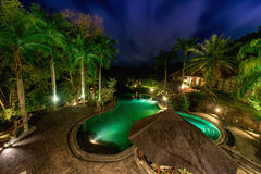 View of infinity swimming pool at luxurious jungle villa. Beautiful garden by night royalty free stock image