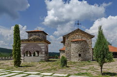 View of inner  yard with old medieval church, alcove and  bell tower  in restored Montenegrin or Giginski monastery. St. St. Cosmas and Damian, mountain  Kitka Royalty Free Stock Images