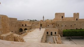 View inside of ancient fortress Ribat of Monastir with trees and walking tourists, Tunisia. Beautiful view inside of ancient fortress Ribat of Monastir with stock video footage