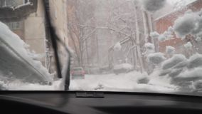 View from inside the car as the janitors clean off snow stock footage