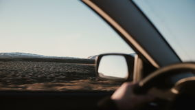 View inside the car on beautiful sunset landscape with mountains covered snow. Close-up view of male hands on the wheel. View inside the car on beautiful stock video