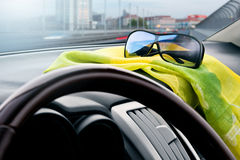View from inside the car on a city road. With the sunglasses in the foreground Royalty Free Stock Photography