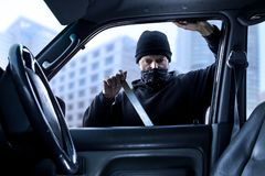 Person,criminal breaking into car in daytime stock image