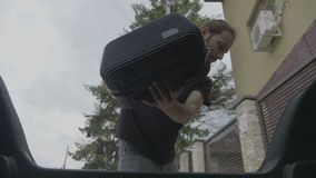 View from inside car of tired young business man arriving from work at home taking his bag from car trunk - stock video