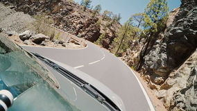 View inside the car to rocky road. Car goes on the serpentine. Footage from two frames. stock footage