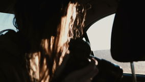 View inside the car. Tourist woman traveling by car and taking photos of sunset landscape outside the window. stock video
