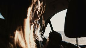 View inside the car. Tourist woman traveling by car and taking photos of sunset landscape outside the window.