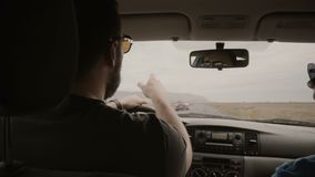 View inside the car. Two man driving the car through the empty road. Friends in sunglasses traveling together. Men riding near the mountains, through the stock video