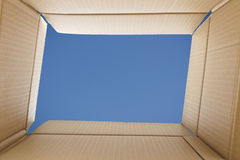 View from inside a cardboard box. Blue sky outside. Freedom concept royalty free stock images