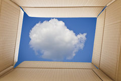 View from inside a cardboard box. Cloud and the sky outside the. Box. Freedom concept royalty free stock photography