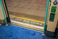 View from inside of London tube train, door opened MIND THE GAP warning written on ground at other side.  stock image
