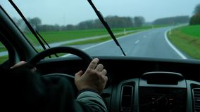 View from from inside, man driving in the rain on lonely highway. View from from inside the car where man with his hand on steering wheel drives in the rain on stock video footage
