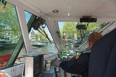 Captain of river boat in Amsterdam. A view inside a river boat with the captain steering the ship in Amsterdam Stock Photos