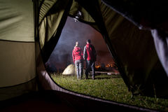 View from inside tent on couple hikers at night camping Royalty Free Stock Photos
