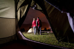 View from inside tent on couple tourist at night camping Royalty Free Stock Photo