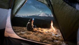 Male tourist have a rest in his camping in the mountains at night under beautiful night sky full of stars and milky way. View from inside a tent on the male Stock Image
