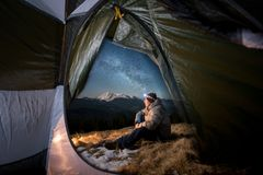 Male tourist have a rest in his camping in the mountains at night under beautiful night sky full of stars and milky way. View from inside a tent on the male Stock Images