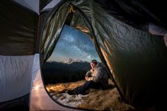 Male tourist have a rest in his camping in the mountains at night under beautiful night sky full of stars and milky way. View from inside a tent on the male Royalty Free Stock Images