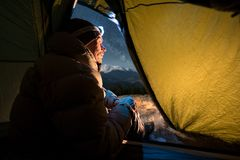 View from inside a tent on the male tourist have a rest in his camping at night Stock Photography