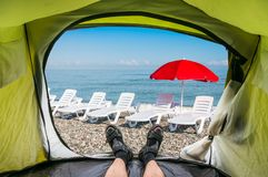 View from inside a tent on the sun loungers on a beach. And red umbrella Stock Images