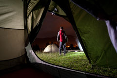 View from inside a tent on tourist standing near camping Royalty Free Stock Image