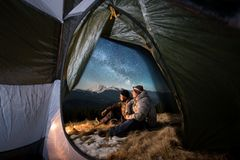 Two male tourists have a rest in the camping in the mountains at night under night sky full of stars and milky way. View from inside a tent on the two male Stock Photo