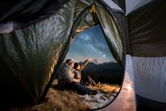 Two tourists have a rest in the camping in the mountains at night Royalty Free Stock Images