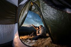Two tourists have a rest in the camping in the mountains at night under night sky full of stars and milky way Stock Photos
