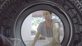 A GoPro view from inside a washing machine of a woman putting in dirty clothes. A view from inside a washing machine of a woman putting in clothes stock video footage