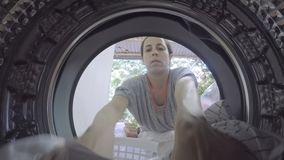 A GoPro view from inside a washing machine of a woman putting in dirty clothes. A view from inside a washing machine of a woman putting in clothes stock video