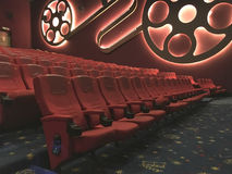 Entertaiment. View of interior cinema hall with rows of red seat in low light condition before the movie starts Royalty Free Stock Photos
